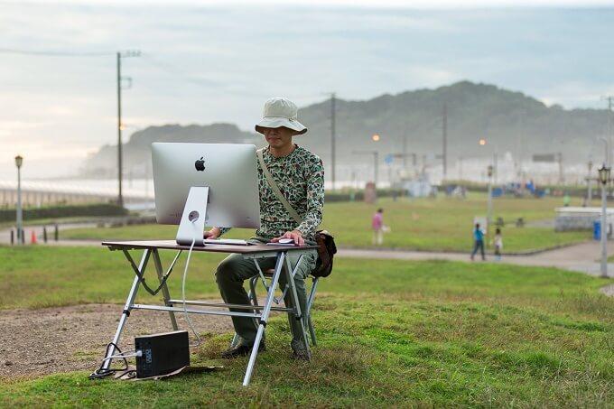 公園でPCを見る男性