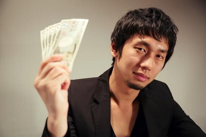 1万円札を持つ男性