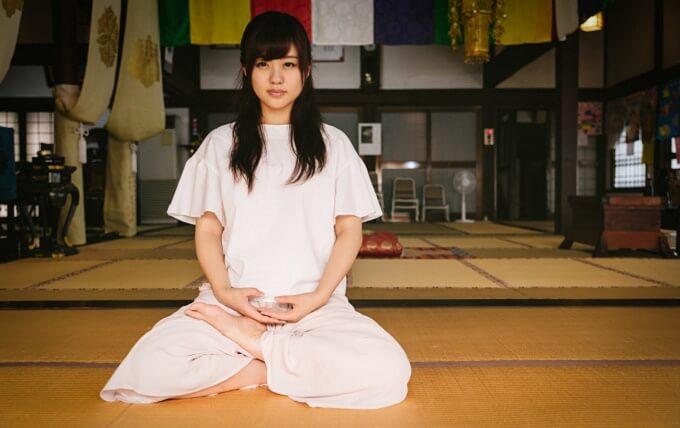お寺で座禅を組む女性